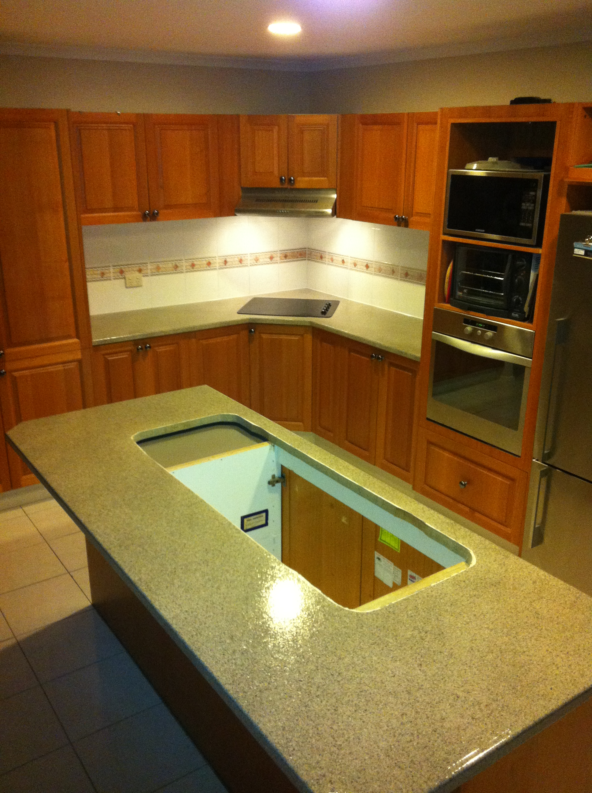 Shaped kitchen with island undergoing renovation (cut out in island